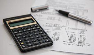 Kalkulator leży na biurku obok dokumentów